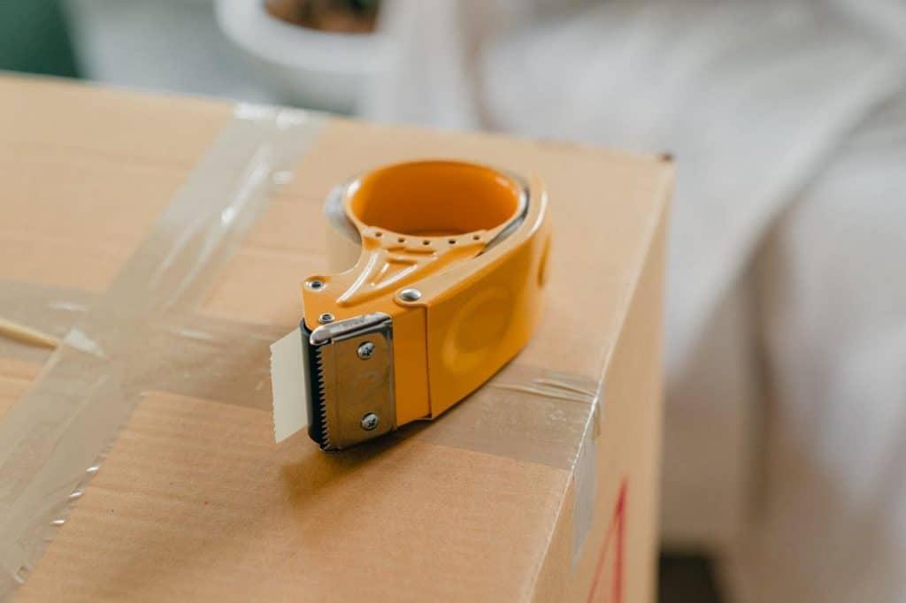 Packing tape gun on a cardboard box.